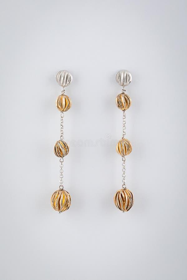 妇女有金黄球的银耳环在链子,隔绝在白色背景 免版税库存图片