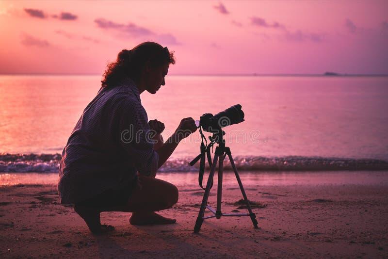 妇女摄影师,为日落照相 免版税库存图片
