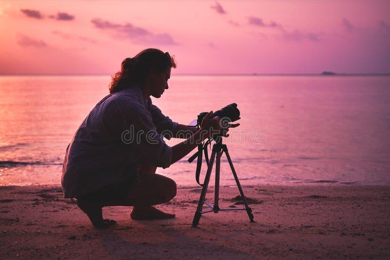 妇女摄影师,为日落照相 免版税库存照片
