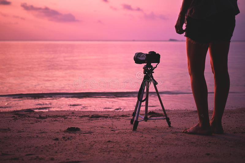妇女摄影师,为日落照相 免版税图库摄影