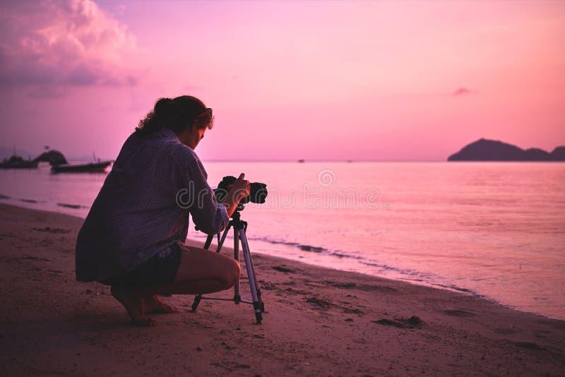妇女摄影师,为日落照相 库存照片