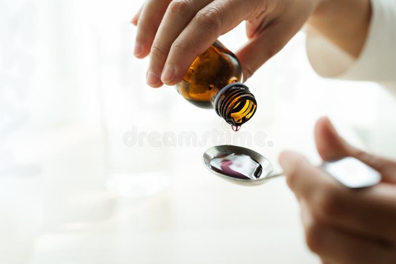 妇女手倾吐的疗程或咳嗽糖浆从捞出的瓶 是概念现有量有医疗保健帮助延迟药片 免版税库存图片