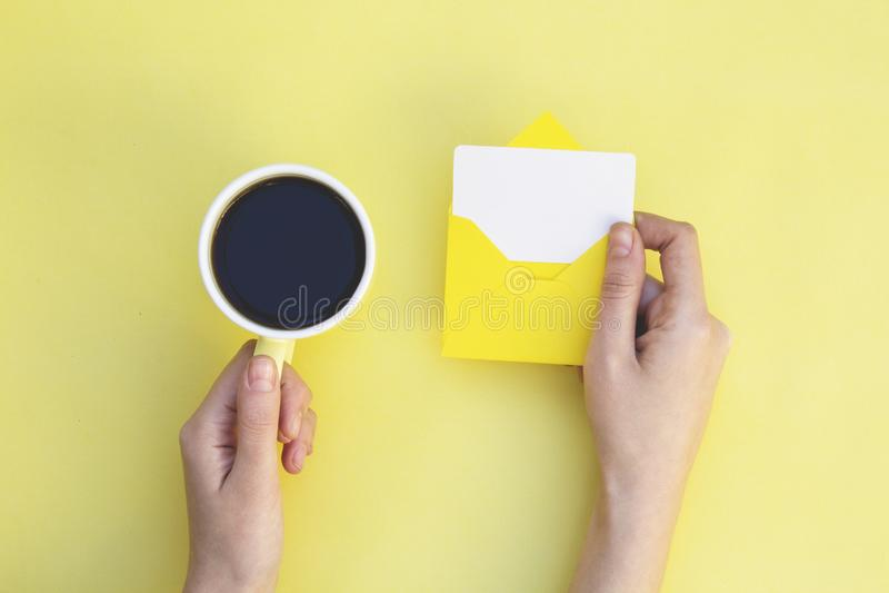 妇女手藏品信封和咖啡杯在黄色背景 库存照片