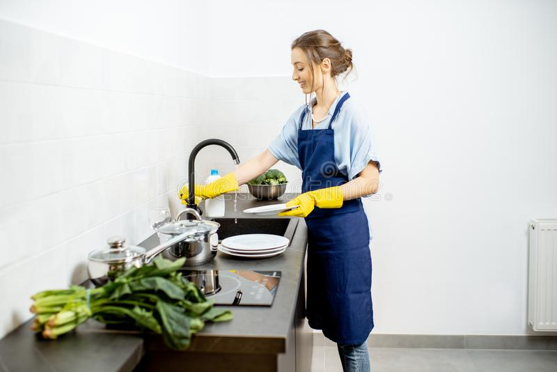 妇女洗碗在家 免版税库存照片