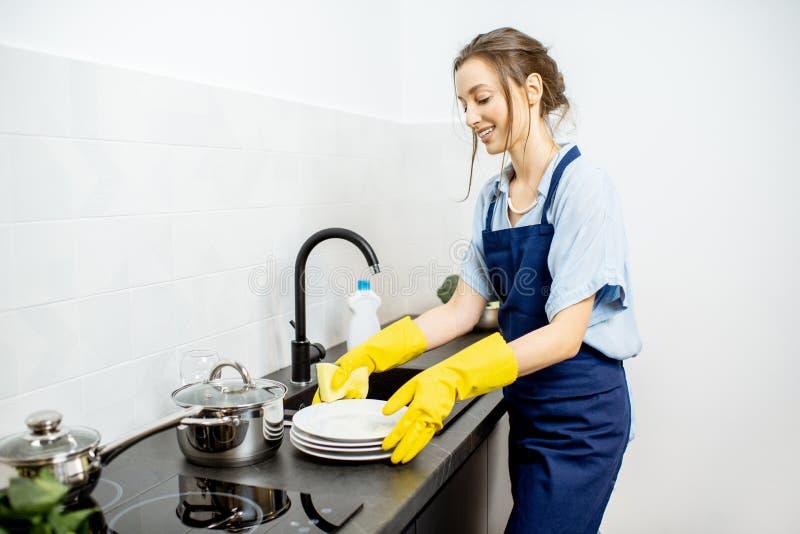 妇女洗碗在家 免版税图库摄影
