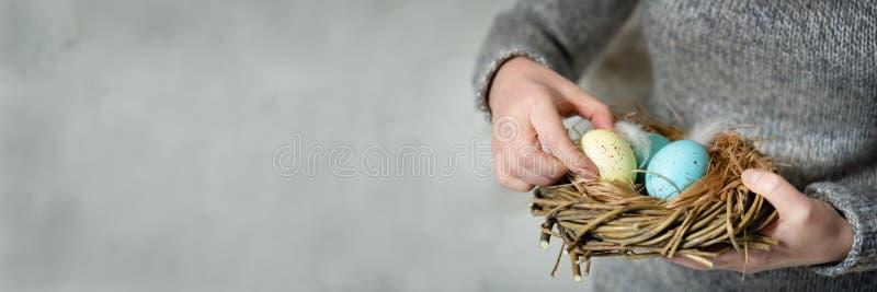 妇女用她的手有很多在巢的明亮地色的复活节彩蛋 库存图片