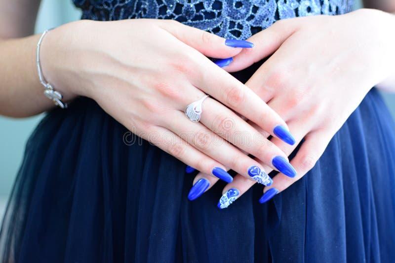 妇女用蓝色礼服横渡的手 库存照片