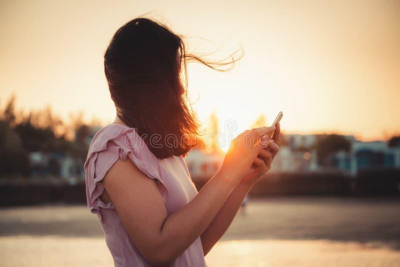 妇女画象在海滩期间暑假使用智能手机,亚裔游人放松与她的在的手机 免版税库存照片