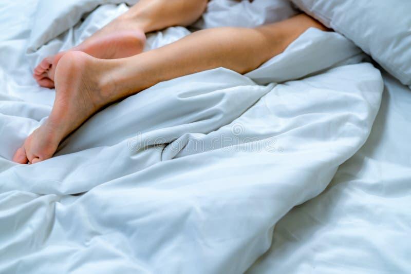 妇女赤脚的关闭在白色毯子和床单的床上在家或旅馆卧室  睡觉和放松概念 库存照片