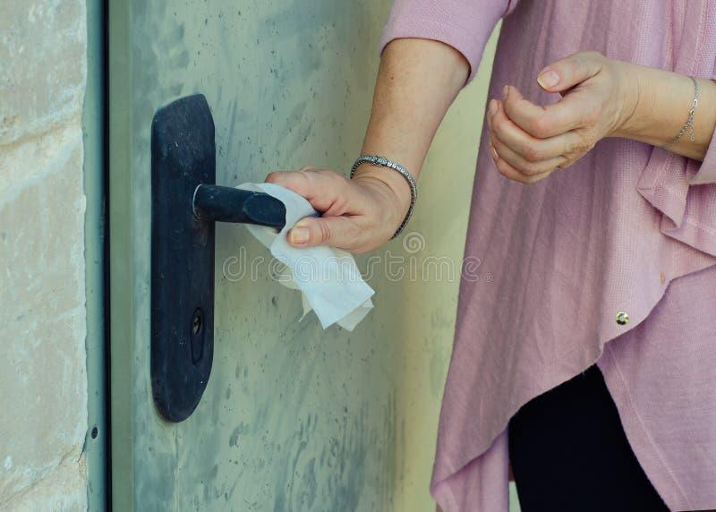 妇女遭受的germophobia新闻肮脏的门把手 免版税图库摄影