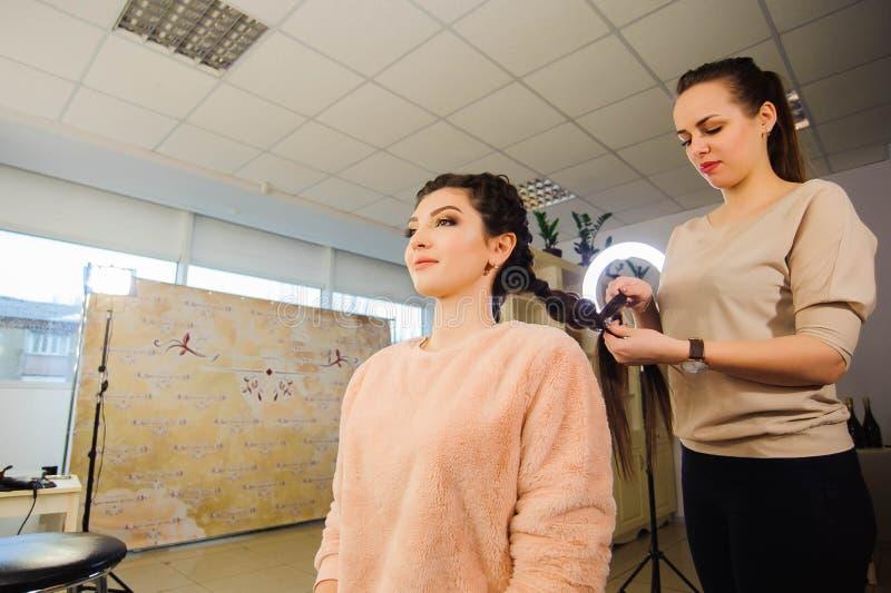 妇女` s理发 美发师,美容院 得到理发的美丽的妇女由美容院的美发师 库存照片