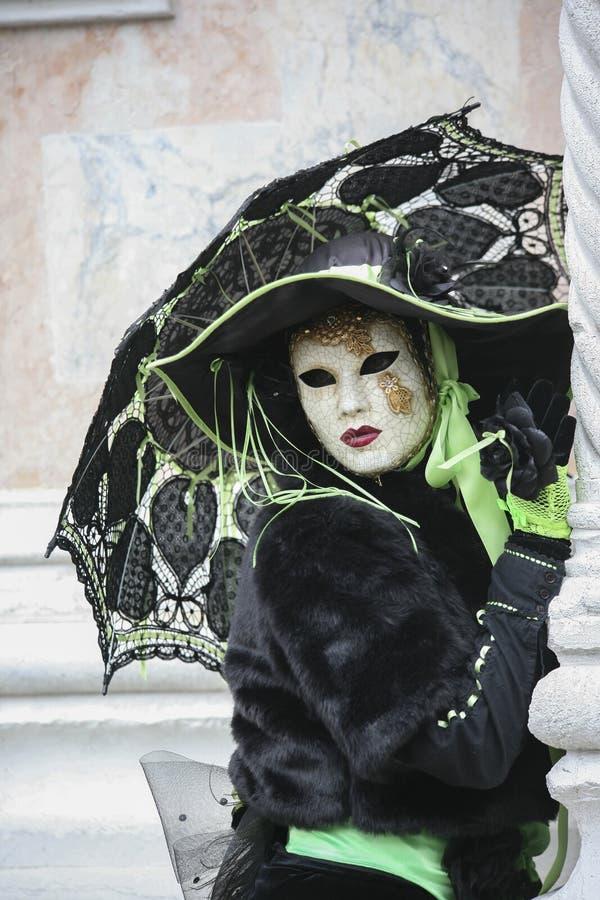 威尼斯在一个五颜六色的黑和绿色和威尼斯式面具穿戴的狂欢节字符威尼斯意大利 免版税图库摄影