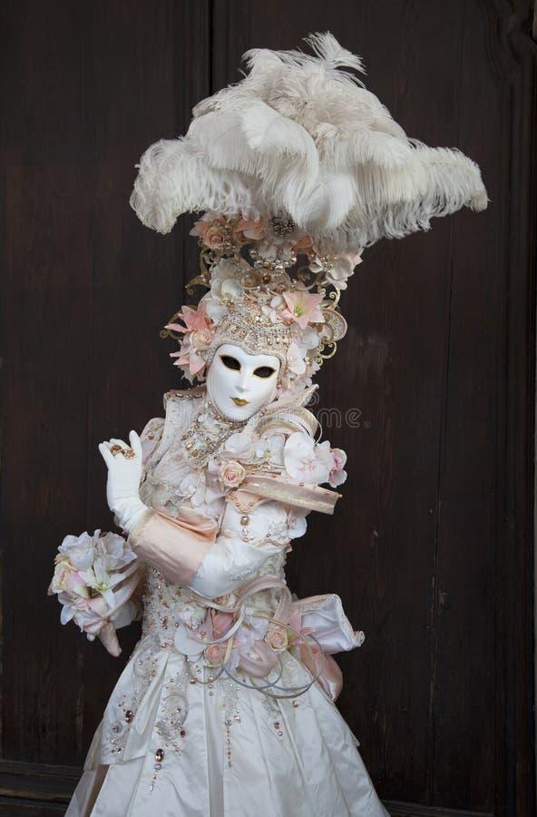 威尼斯戴着五颜六色的桃子&白色服装和威尼斯式面具威尼斯意大利的狂欢节形象 免版税库存图片
