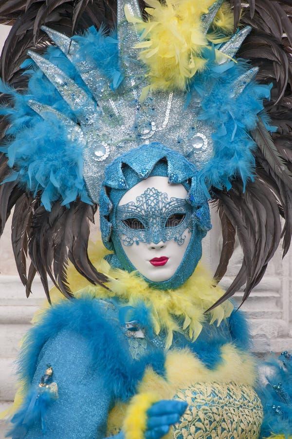 威尼斯戴着五颜六色的蓝色,黄色和黑服装和威尼斯式面具威尼斯意大利的狂欢节形象 免版税库存图片