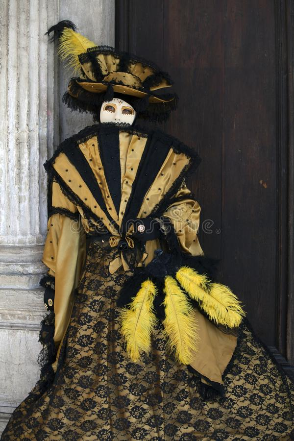 威尼斯戴着五颜六色的金子和黑服装和威尼斯式面具与爱好者威尼斯意大利的狂欢节形象 免版税库存照片