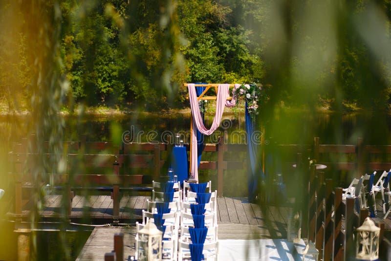 婚礼的曲拱,装饰用美丽的鲜花和布料 注册在婚姻地方  库存图片