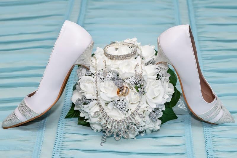 婚礼辅助部件 在一双新娘花束、耳环、镯子、项链和新娘鞋子的两结婚戒指 免版税库存照片