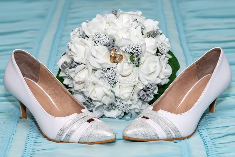 婚礼辅助部件 在一双新娘花束和新娘鞋子的两结婚戒指 免版税库存照片