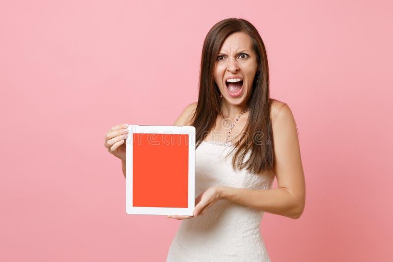 婚纱尖叫的举行平板电脑计算机的恼怒的被激怒的新娘妇女有空白黑空的屏幕的  图库摄影