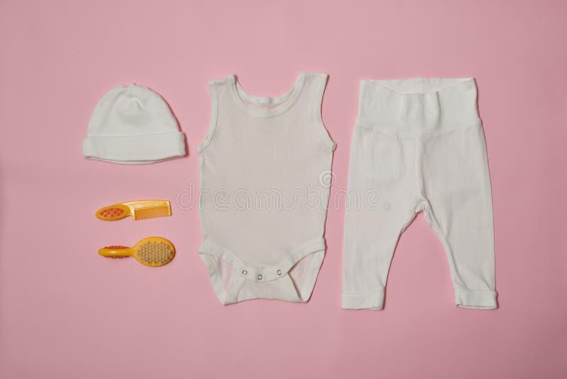 婴孩在桃红色背景的时尚概念 衣物和辅助部件关心的 免版税库存照片
