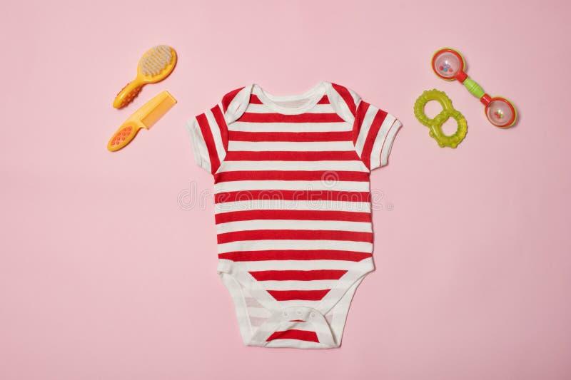 婴孩在桃红色背景的时尚概念 镶边紧身衣裤、扇贝和装豆子小布袋 免版税库存照片