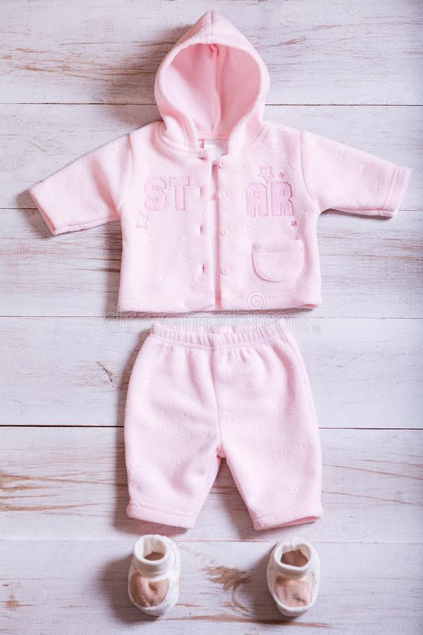 婴孩衣裳和辅助部件在白色木背景桌,桃红色儿童新出生的时装集合上女孩的,现代孩子婴儿 库存图片