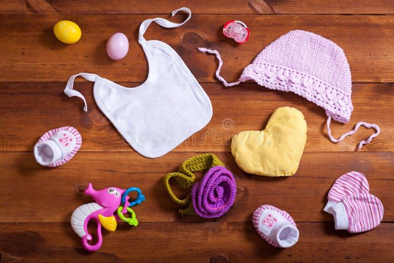 婴孩衣裳辅助部件集合、桃红色被编织的棉花衣物、玩具和孩子围嘴在棕色木背景,儿童新出生的布料为 免版税图库摄影