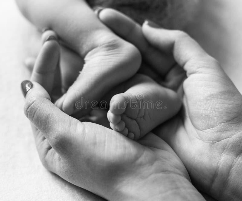 婴孩脚托起入母亲手 脚和脚跟的柔和的被弄脏的背景新出生 免版税库存照片
