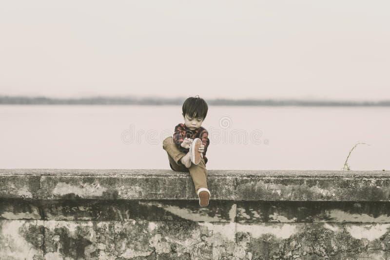 孤独的孩子离开鞋子,并且他坐地面 图库摄影