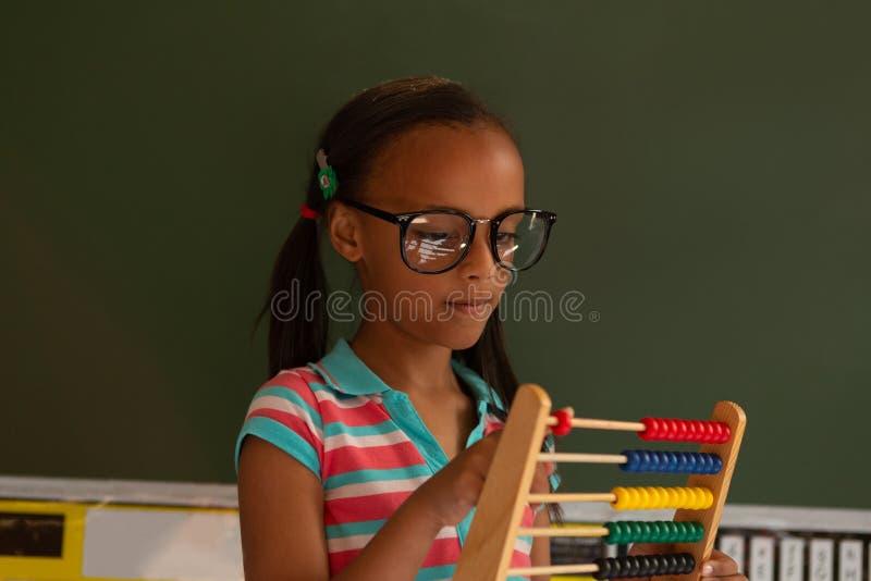 学会与算盘的女小学生数学在教室 库存照片