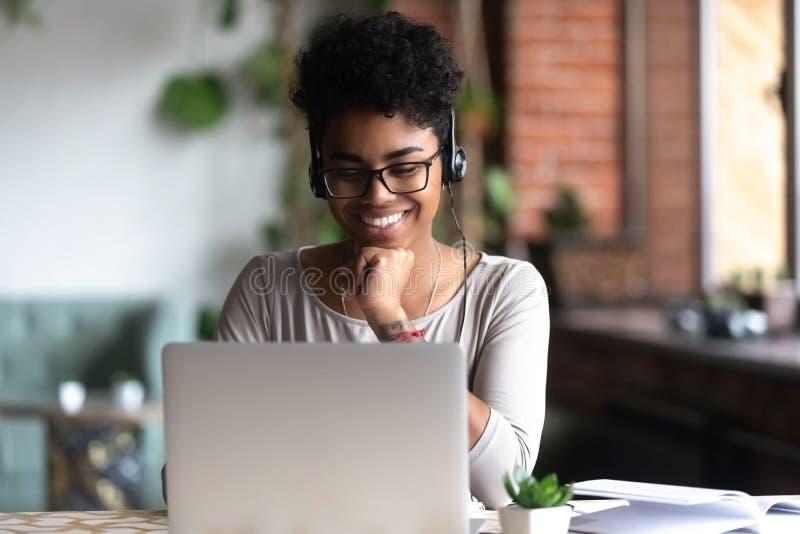 学会使用互联网和耳机的聪明的学生 库存图片