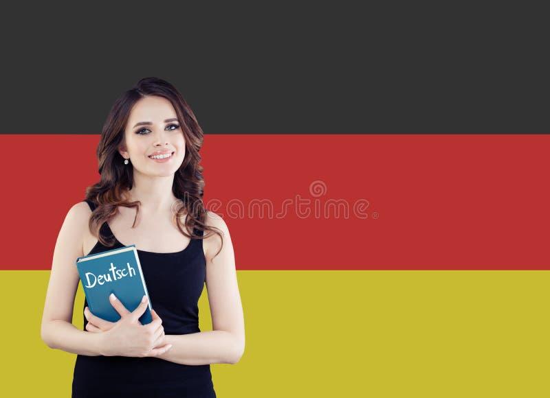 学会德语 拿着phrasebook的可爱的年轻女人反对德国旗子背景 免版税图库摄影