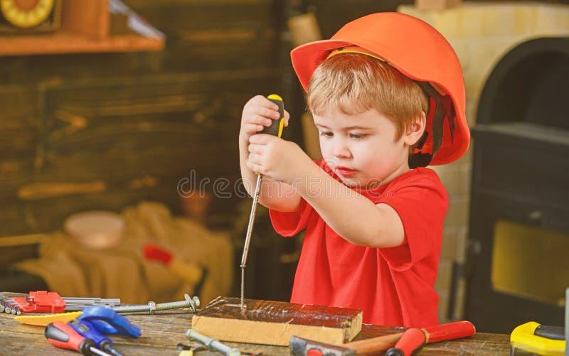 学会的孩子使用螺丝刀 在运作在车间的橙色盔甲的被集中的孩子 未来职业概念 免版税库存图片