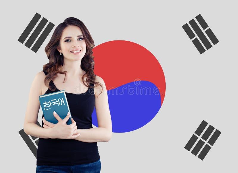 学会韩语 有书的俏丽的年轻女人学生反对韩国旗子背景 免版税图库摄影