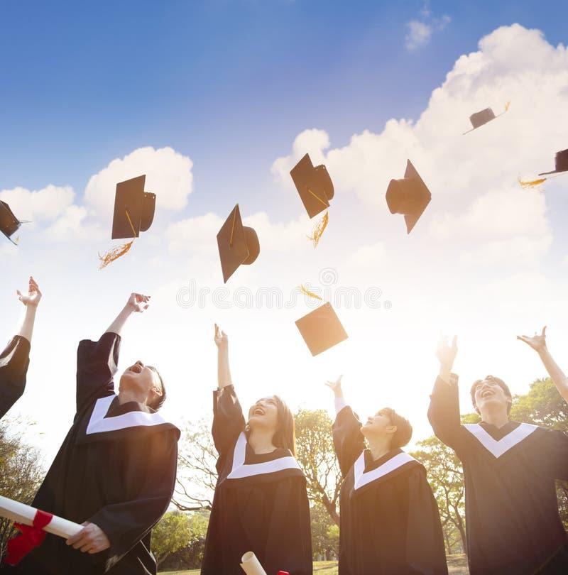 学生在天空中的投掷毕业盖帽 免版税库存照片