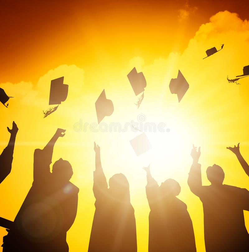 学生在天空中的投掷毕业盖帽 免版税库存图片
