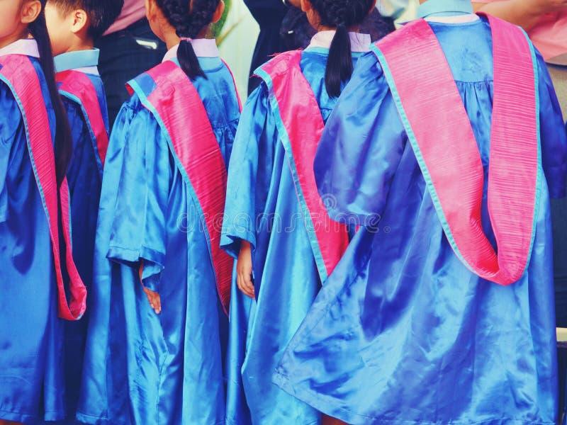 学龄前孩子佩带的毕业礼服关闭  免版税图库摄影