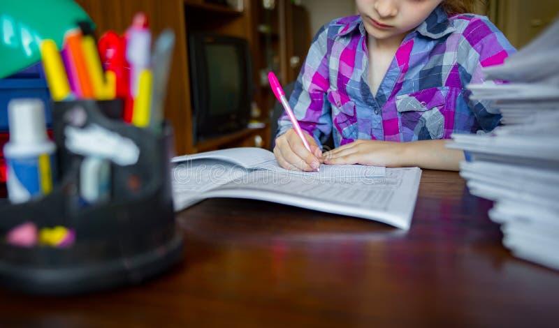孩子做他的家庭作业,写和学会 写的特写镜头在手边 免版税库存照片