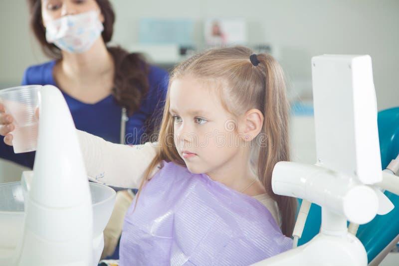 孩子在牙医椅子漂洗嘴并且坐 免版税库存图片