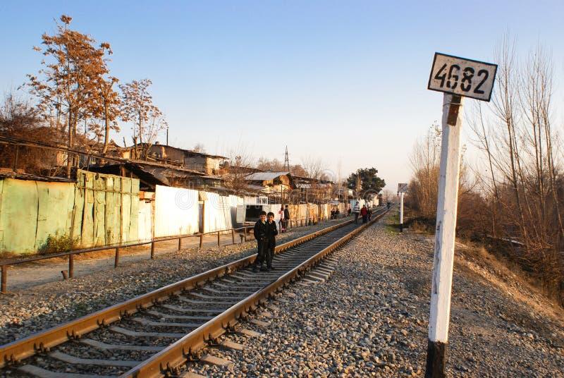 孩子沿铁路穿过走杜尚别  塔吉克斯坦 25 12 2010年 免版税库存图片