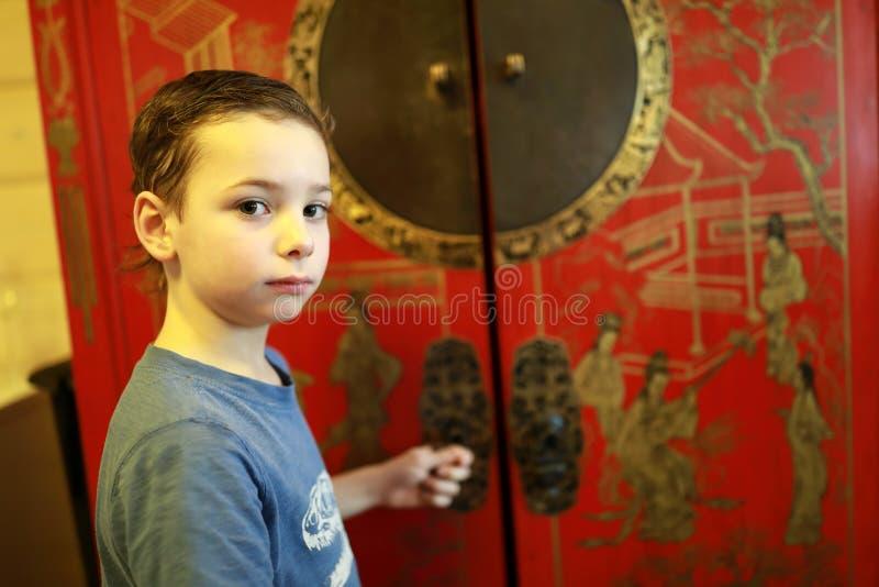 孩子打开中国碗柜 图库摄影