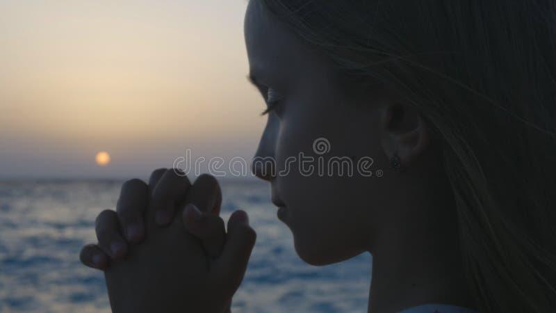 孩子祈祷在海滩的在日落,周道的祷告孩子,海边的沉思女孩 库存照片