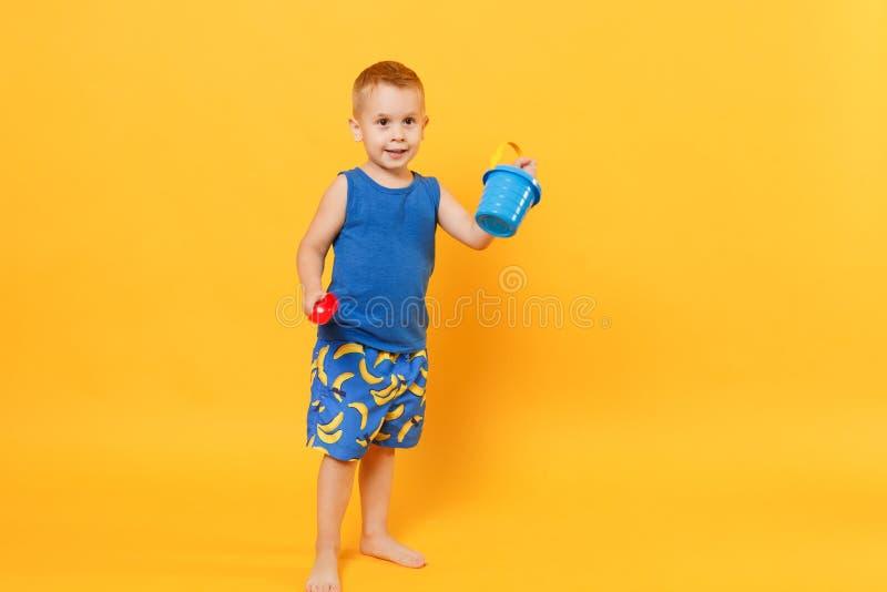 孩子男孩乐趣在蓝色海滩夏天衣裳的3-4岁拿着沙子玩具被隔绝在明亮的橙黄墙壁背景 库存照片