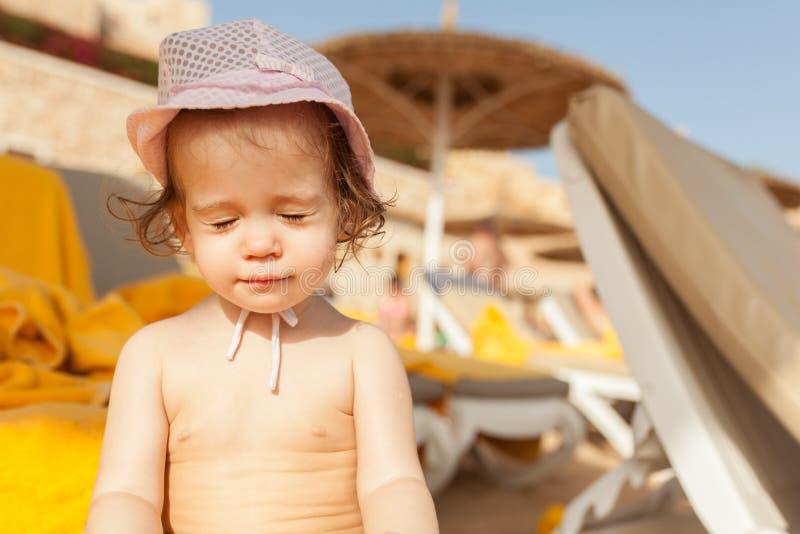 孩子闭上了他的从太阳的眼睛在海滩 库存照片
