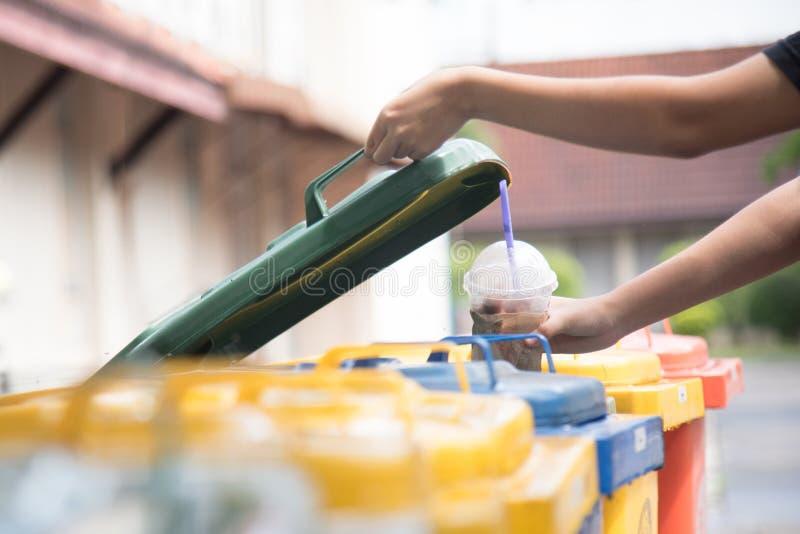 孩子递投掷的空的塑料瓶入垃圾 保存的环境通过投掷塑料jung对回收站或 免版税库存图片