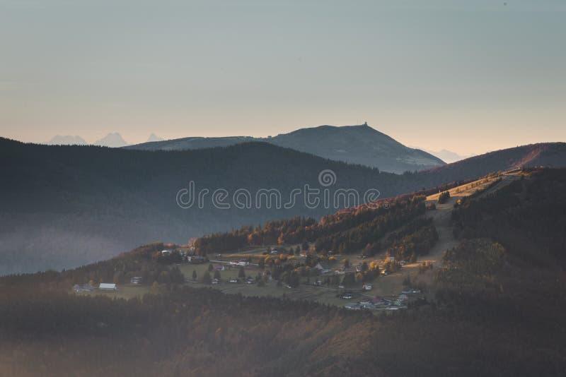 孚日省山的村庄在与上升从森林阿尔卑斯的雾的清早阳光下在背景中 库存照片