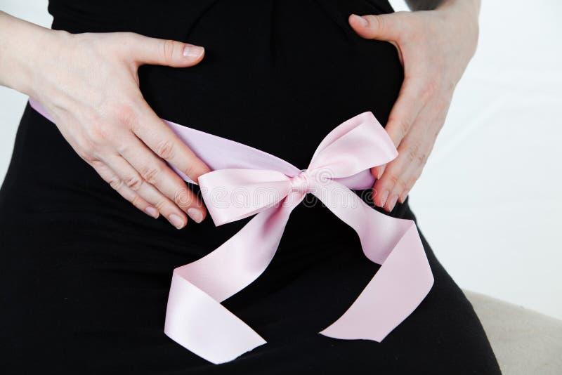 孕妇的腹部有桃红色丝带的-怀孕健康母性 图库摄影