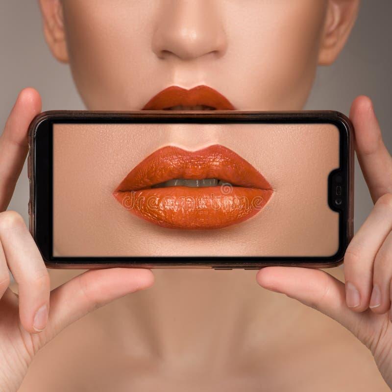 宏观完善的嘴唇构成 面孔的细节的宏观照片 桔子唇膏树荫  库存照片