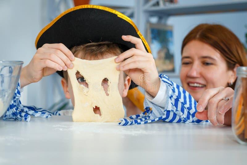 家庭一起烹调 妈妈和儿子揉面团用面粉 在厨房里准备面团 免版税库存照片