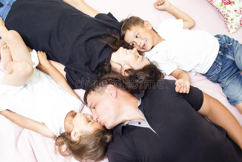 家庭价值观 愉快的白种人四口之家获得乐趣,当说谎在沙发户内时 图库摄影